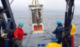 MBARI researchers lower the Environmental Sample Processor (protected by a cylindrical waterproof housing) into the waters of Monterey Bay. Image: © 2006 MBARI