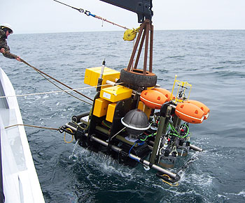 The crew of MBARI's research vessel Point Lobos lower the Benthic Rover over the side of the ship and into the waters of Monterey Bay. Image: © 2009 MBARI