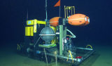 "The Benthic Rover makes its way across the deep seafloor during a trial run in 2007. The ""brains"" of the vehicle are protected by a spherical titanium pressure housing. The orange and yellow objects are made of incompressible foam, whose buoyancy makes the Rover light enough underwater so that it won't sink into the soft deep-sea mud. Image: © 2007 MBARI"