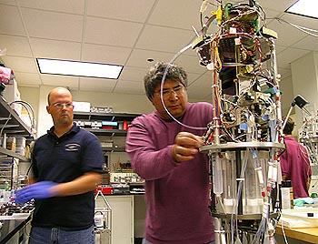 The Environmental Sample Processor (ESP) is a unique instrument that can detect specific types of microscopic plants and animals in seawater by analyzing their DNA. In this photograph, MBARI researchers Joe Jones (left) and Roman Marin III (right) prepare the ESP for deployment in Monterey Bay. Photo: Kim Fulton-Bennett (c) 2004 MBARI