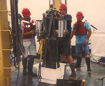 Researchers collect a box core of sediment from the Santa Barbara Basin. To collect a box core, a metal box, about a meter and a half long and 20 centimeters wide, is lowered down to the sea bottom, where it sinks into the soft sediment. After the box core is brought back to the surface, undisturbed layers of sediment can be collected from the inner portion of the core. Image: (c) 1997 Vicente Ferreira-Bartrina