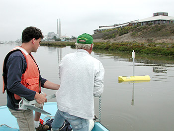 MBARI's Joe Needoba and Steve Fitzwater deploy the new LOBO mooring in a tidal section of the old Salinas River channel. Photo: Ken Johnson (c) 2004 MBARI
