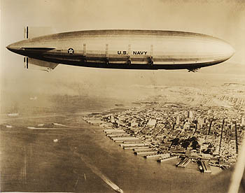 "Like its sister ship, the USS Akron (shown here flying over the city of San Francisco) the USS Macon was a familiar sight across the United States. Thousands of people would turn out to observe the ""flying aircraft carrier"" conducting training maneuvers. The USS Macon carried four biplanes on board. Credit: Wiley Collection, Monterey Maritime & History Museum"