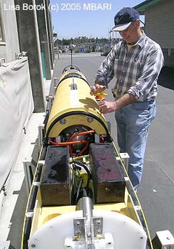 AUV specialist Duane Thompson working on the middle compartment of the mapping AUV, which contains the mapping sonar equipment. Image: Lisa Borok (c) 2005 MBARI