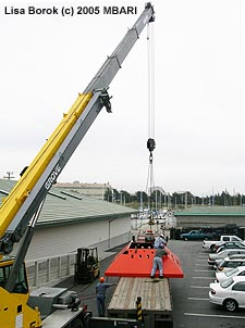 In May 2005, the trawl-resistent frame for the MARS node was delivered to MBARI on a large flatbed truck. This was no easy ride, since the frame is about twelve feet wide, fifteen feet long, and four feet tall. Here the frame is waiting to be transferred into a staging area at MBARI (the cars nearby had to be moved first). Image: Lisa Borok (c) 2005 MBARI