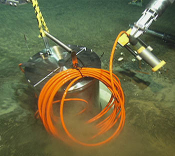 This image taken by ROV Ventana shows the MOBB seismometer being lowered into a plastic sleeve in the seafloor, about 1,000 meters below the surface of Monterey Bay. The seismometer was buried in the seafloor to shield it from the tiny vibrations caused by ocean-bottom currents and waves at the ocean surface. Image: (c) 2002 MBARI