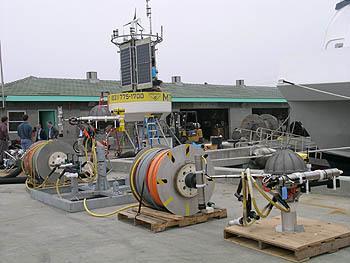 This photo shows some of the components of the Shepard Meander observatory hooked up on the MBARI dock for testing prior to deployment. The large buoy in the background floats at the surface, but all the other instruments and orange cables now sit on the seafloor 3,200 meters below the ocean surface. Image: Kim Fulton-Bennett (c) 2006 MBARI