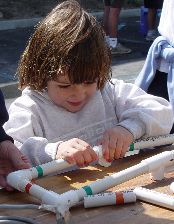 A young girl concentrates on building her own remotely operated vehicle out of PVC pipe. Photo: Duane Thompson (c) 2004 MBARI