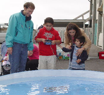 MBARI engineer Brent Roman, left, helps a family test a small remotely operated vehicle (ROV) that they made themselves. Photo: Duane Thompson (c) 2004 MBARI