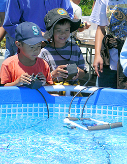 Two boys test out a small remotely operated vehicle that they assembled using PVC pipe and small electric motors. Photo: Heather Fulton-Bennett (c) 2007 MBARI