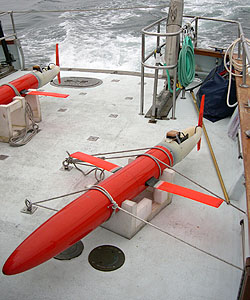 An undersea glider from the Scripps Institution of Oceanography is carried on board a research vessel out to the MB06 study area northwest of Monterey Bay. Image: (c) 2003 MBARI
