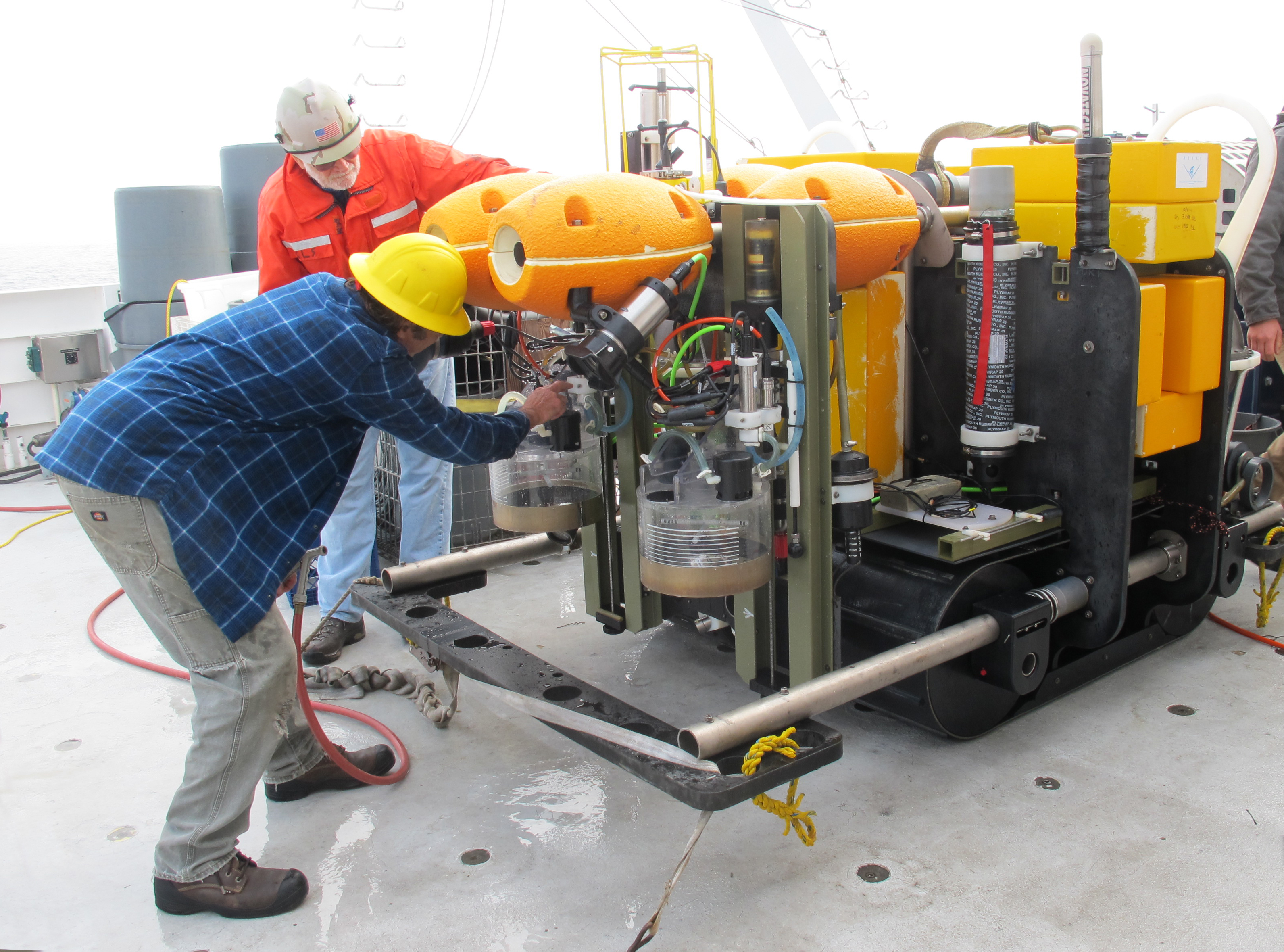 Ken Smith in red and John Ferreira in blue are inspecting the Rover on the deck of the R/V <em>Western Flyer</em>