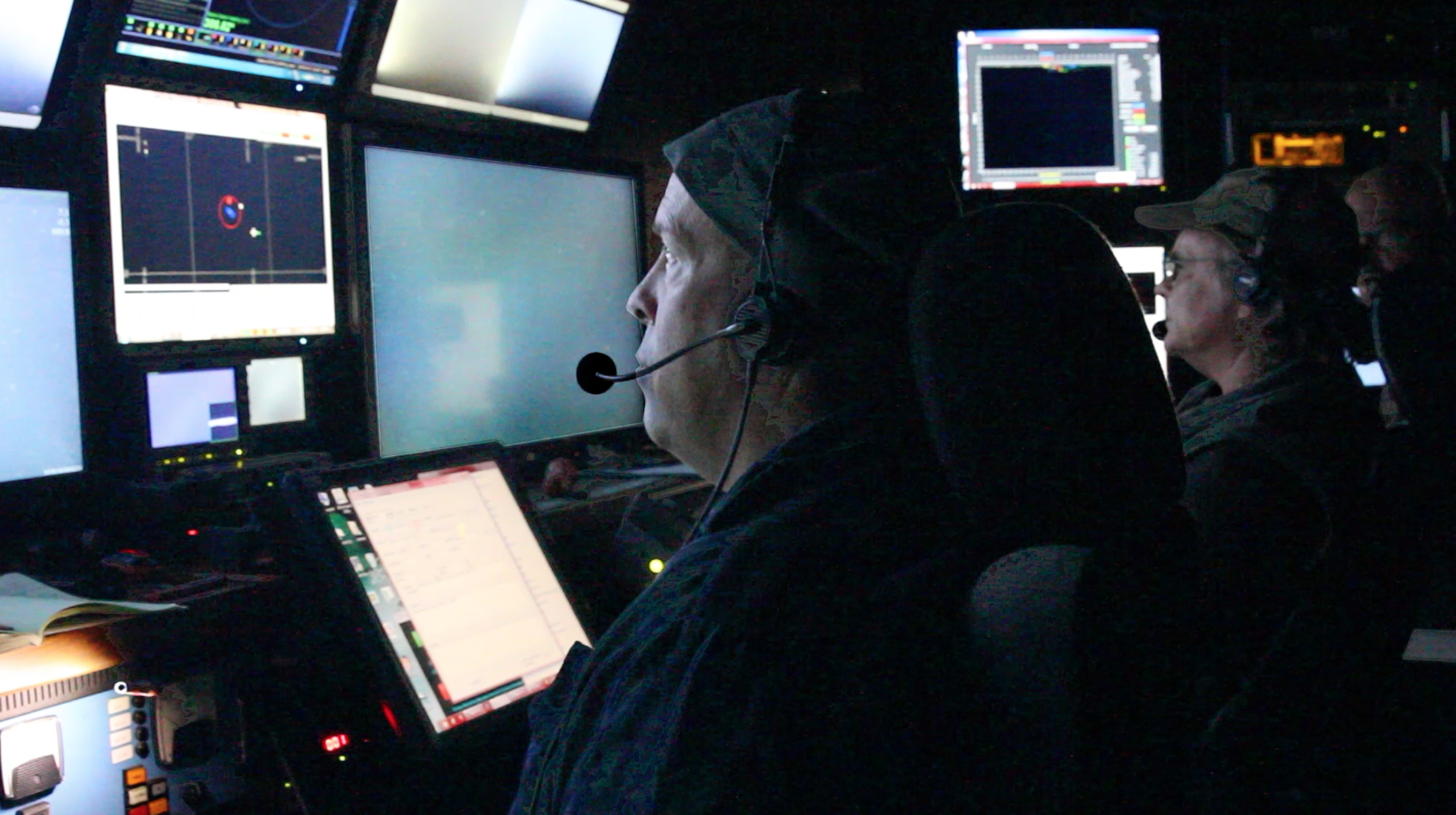 ROV Pilot DJ Osborne and Researchers Kim Reisenbichler and Rob Sherlock work together in the control room of the R/V <em>Rachel Carson</em> to conduct survey transects with the ROV.