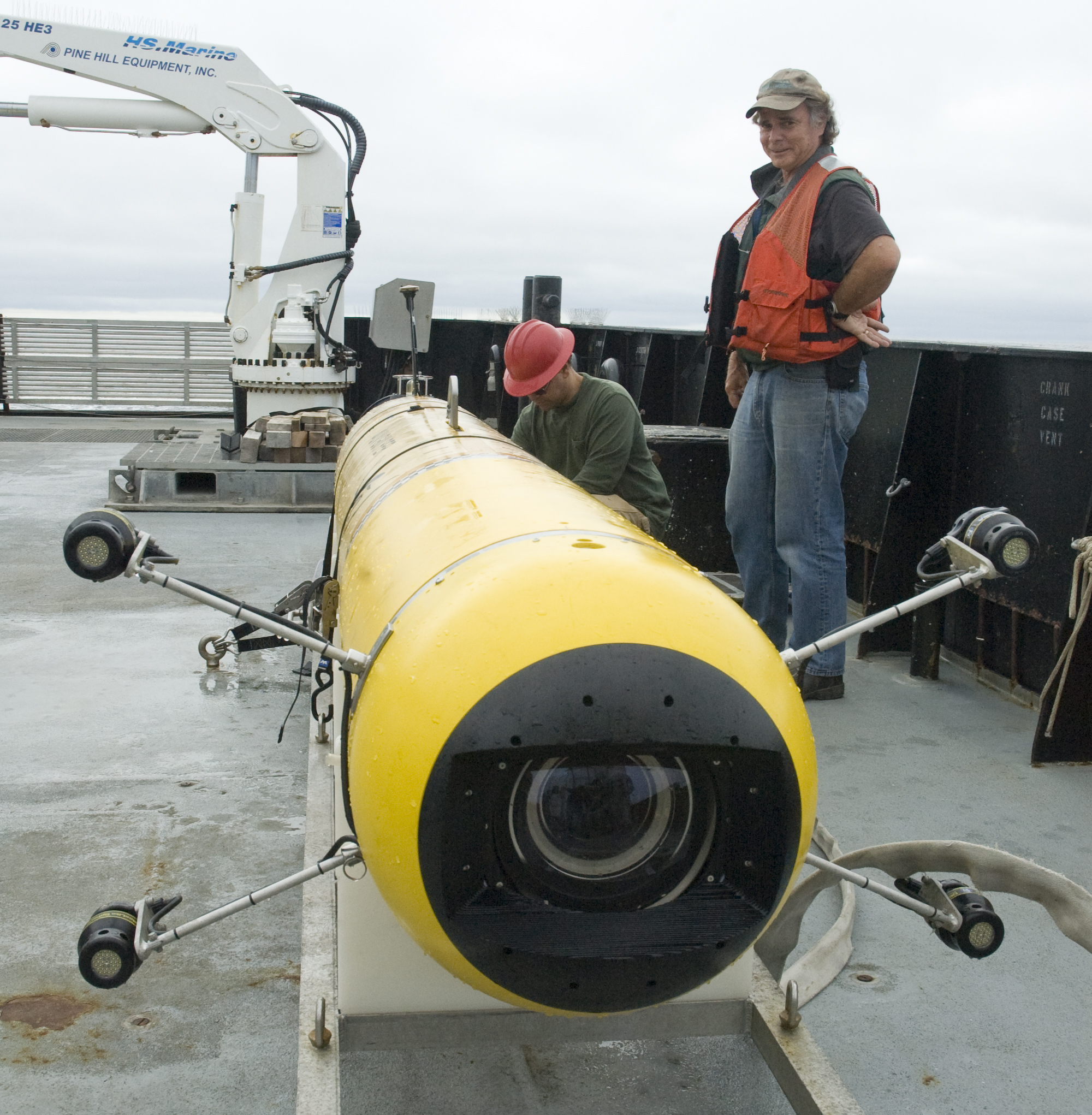 Research Specialist Kim Reisenbichler and AUV Group Leader Hans Thomas look over the i2MAP AUV as it sits on its cradle on the deck of the R/V <em>Rachel Carson</em>.