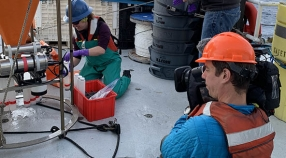 Woman collecting samples on ship deck with man in hard hat and life vest filming her.